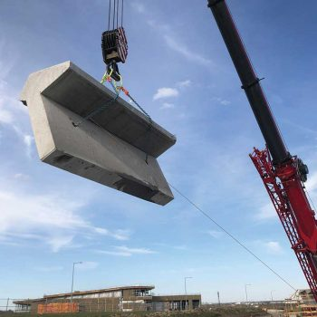 Concrete company edmonton - walser contracting lifting a large piece of concrete into position with a crane